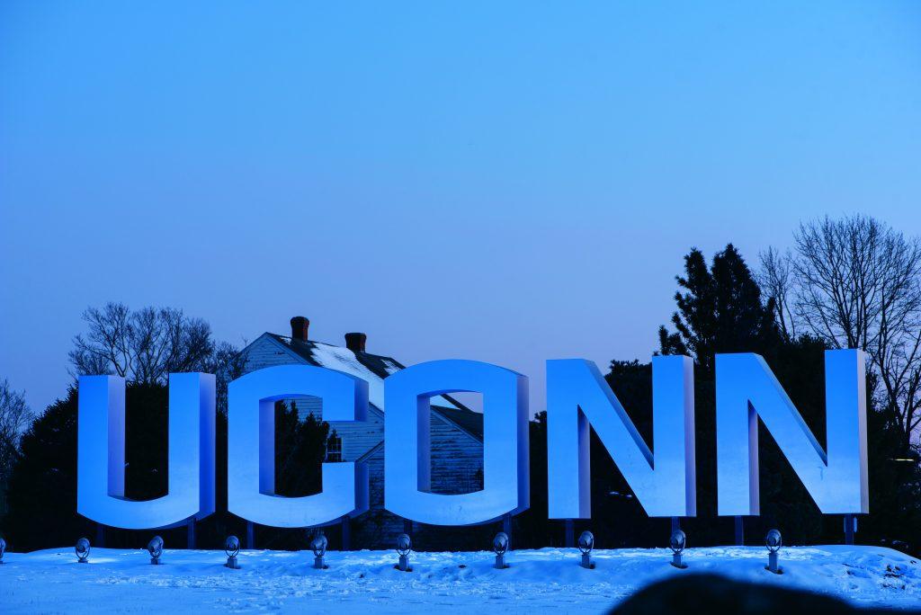UConn gateway sign lit up at dusk