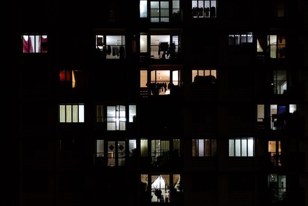 Photo of apartment windows lit up at night.