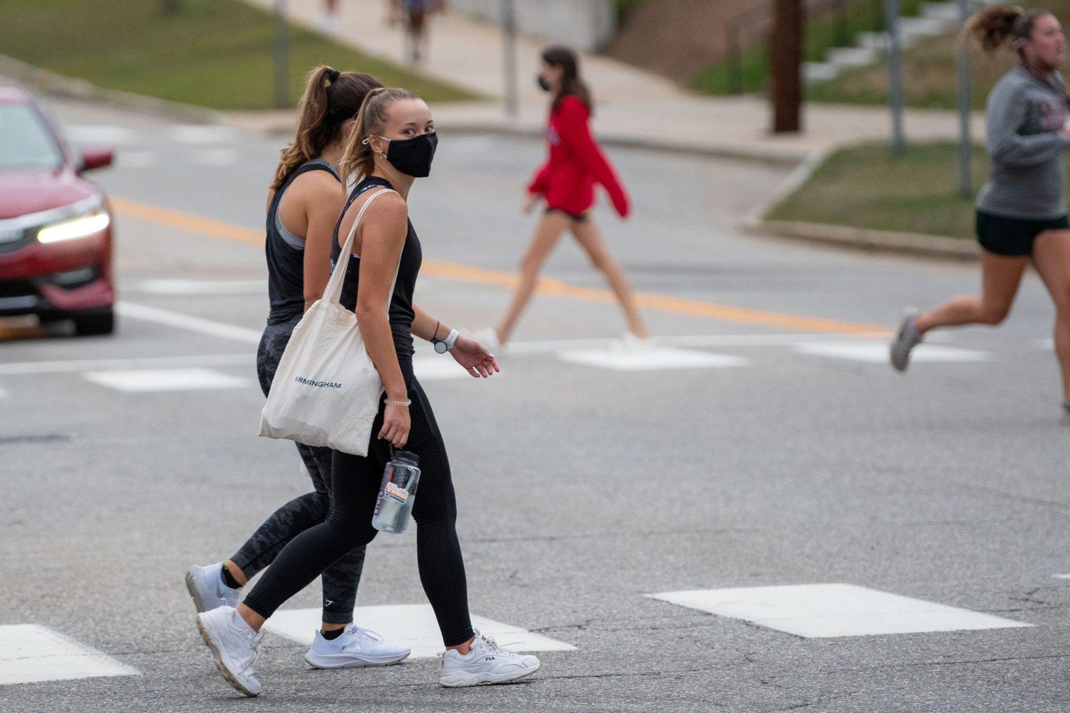 Girls walking in a crosswalk on campus